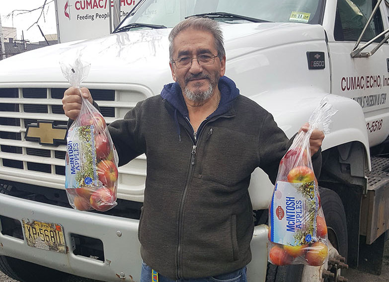 bert, cumac's senior driver, holding fresh produce from his morning pick up.