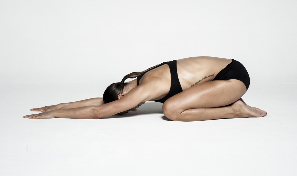 REST POSITION - Sit back onto your heels with your knees slightly apart in a comfortable position and reach your arms forwards. Really focus on pushing yourself back onto your heels stretching out your lower back and glutes. You can walk your hands around to either side of your body to stretch out each side of your body.