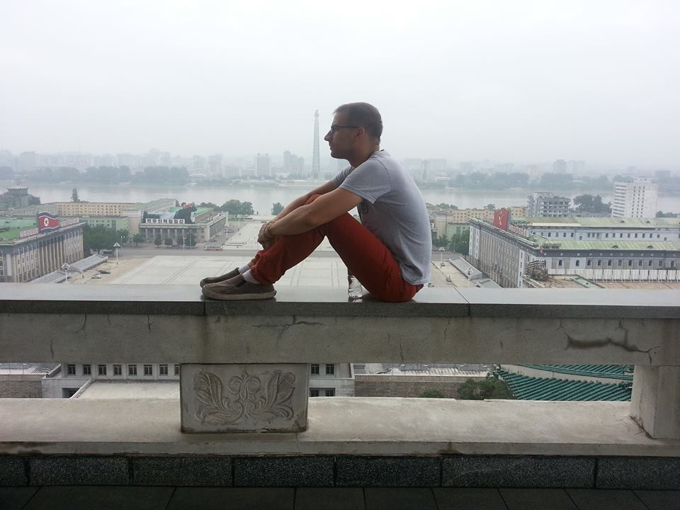 Pyeongyang, North Korea - In 2013, I was granted the rare North Korean visa. Here, atop Kim Il-Sung Square, I sit where Kim Jong-Un can be seen viewing military parades below.