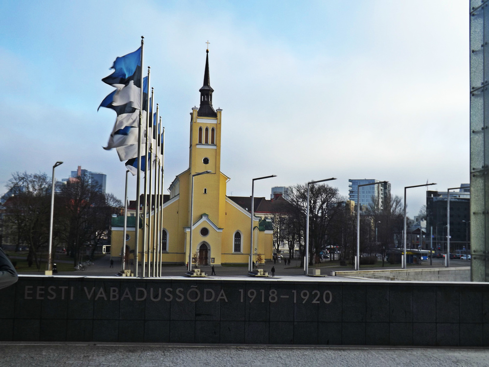 Yellow Tallinn Building with Estonian Flags | Tall Girl Meets World