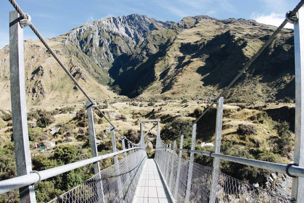 Crossing over the swing bridge on the way back during the Rob Roy Glacier Hike, New Zealand.