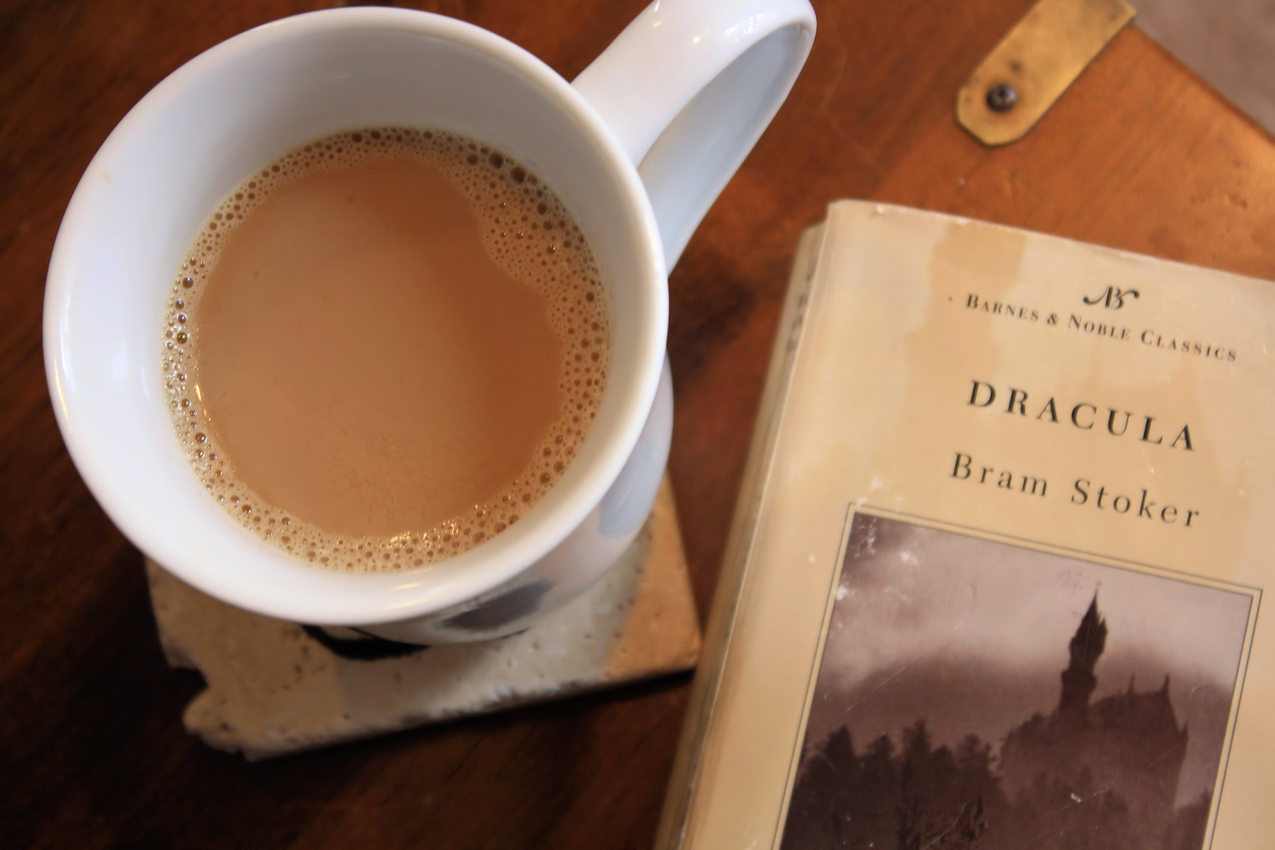 Photo of Bram Stoker's Dracula book and cup of coffee by TorchFire Studio