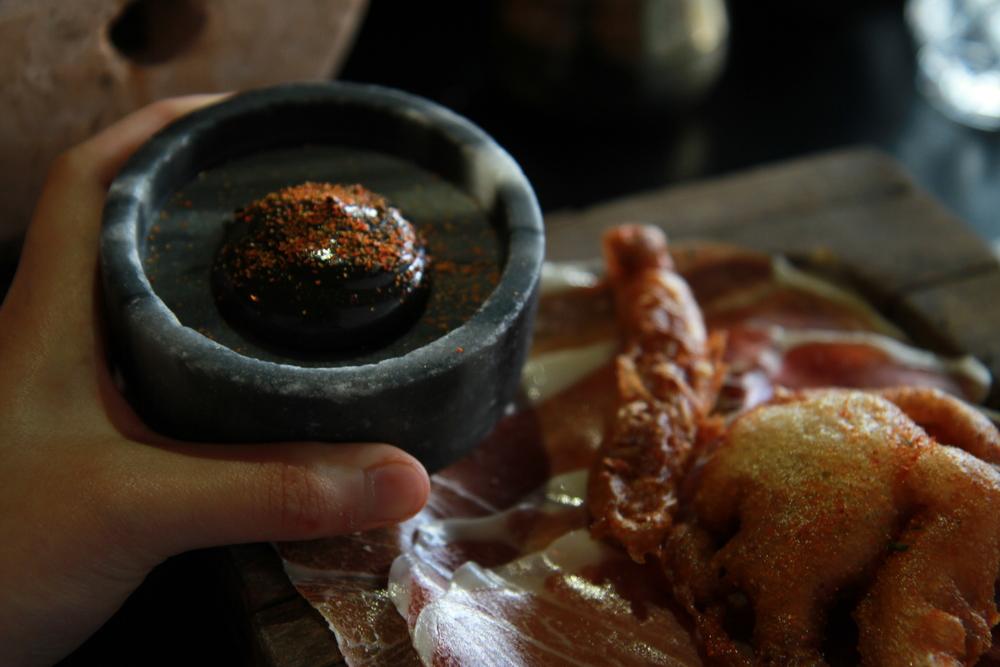Jamón Ibérico with Squid tempura and Black aioli (Thịt lợn muối ăn kèm với Tempura mực và aioli màu đen. Aioli làm từ tỏi, trứng và dầu oliu)