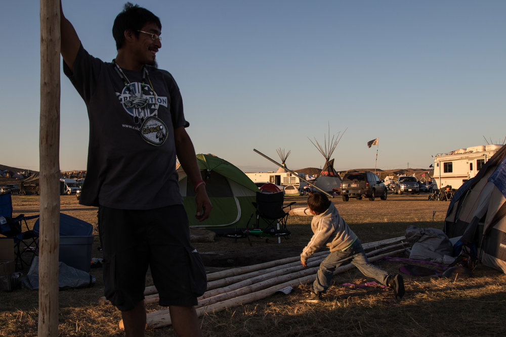 Kaslin throws a metal dowel like a spear while roughhousing with a friend at the Dakota Access Pipeline protest camp. (Jackson Barnett)