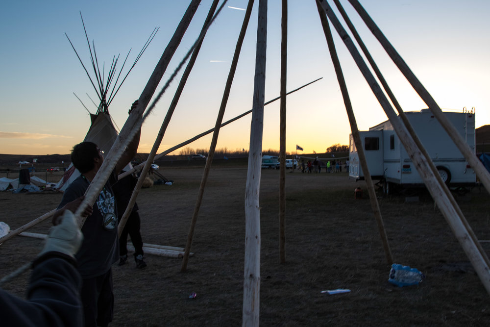 After a few hours of struggling, David, Sage and Jesse finish the frame of David's teepee at the Dakota Access Pipeline protest camp. (Jackson Barnett)