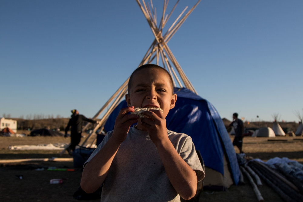 Kaslin's friend bites into a raw ramen packet as David and Sage build a teepee in the background. (Jackson Barnett)