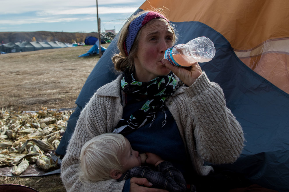 "A mother breast feeds her child in the camp, calling the protest camp the ""intentional community"" she was looking for her family, taken on Oct. 22. (Jackson Barnett/CU Independent)"