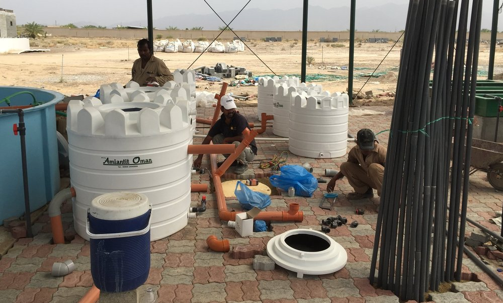Construction staff assemble plumbing parts for this aquaponics system in Oman.