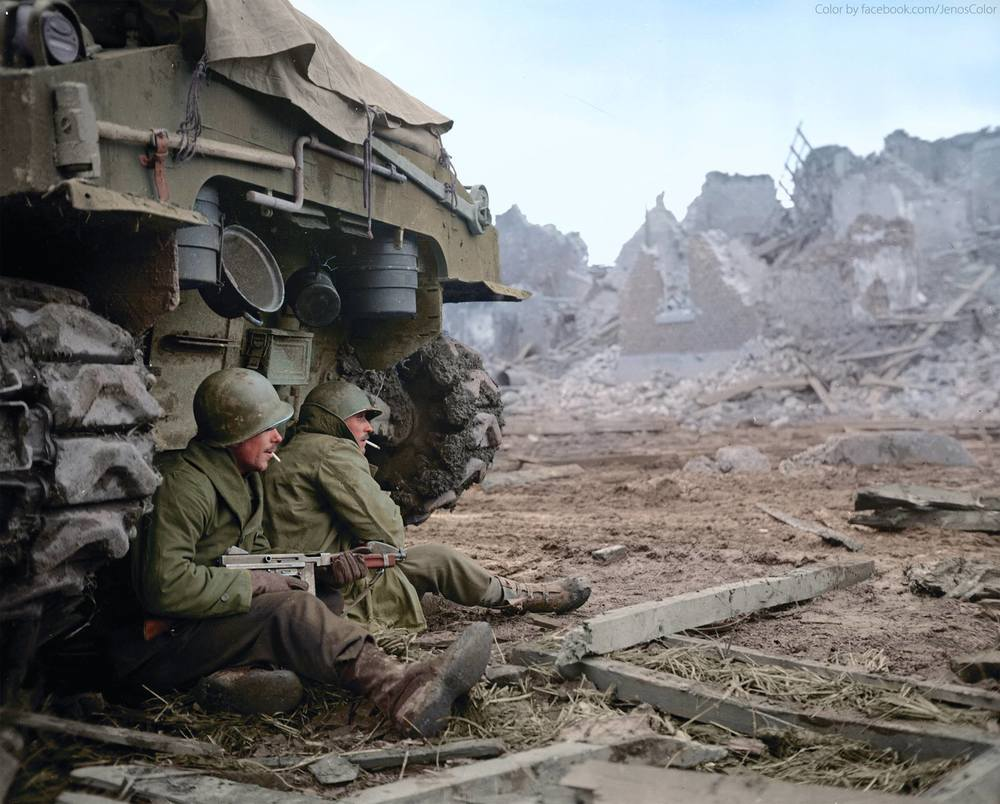 Near the end of World War II in a devastated German town, two soldiers huddle under the cover of a US Sherman tank perhaps getting some warmth from it's engine in the cold winter of 1944-5. One cradles a Thompson submachine gun cocked and ready in his lap. As in so many photos of the era, they wear their helmets tipped coolly to one side, and cigarettes from their C Ration kits dangle from their lips.