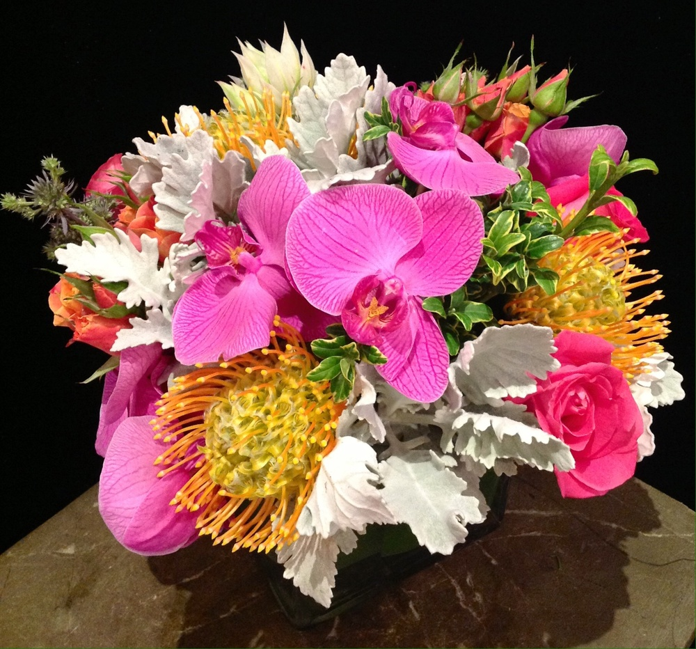 Magenta Phalaenopsis Orchid, Yellow Pincushion, Hot Pink Roses, Two-tone Orange Spray Roses, & Dusty Miller