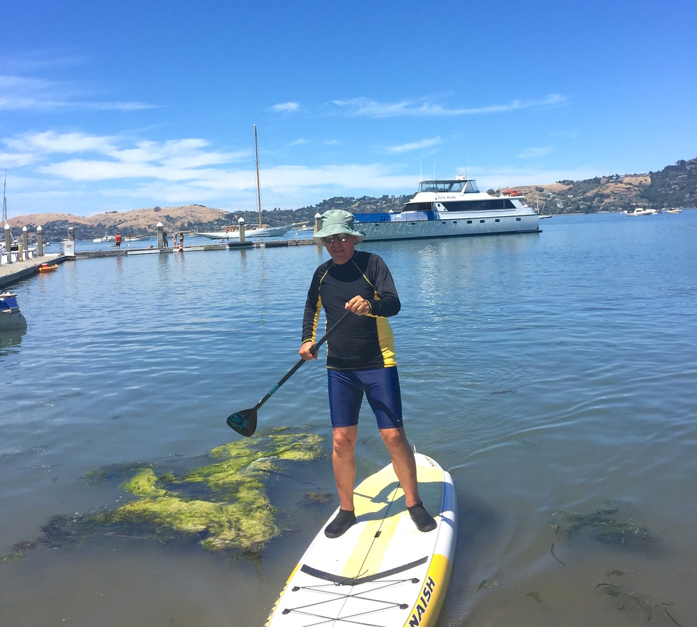 Co-Host Gregg McVicar comes in for a beach landing while paddle boarding with friends. Photo: Gabriela Castelán.