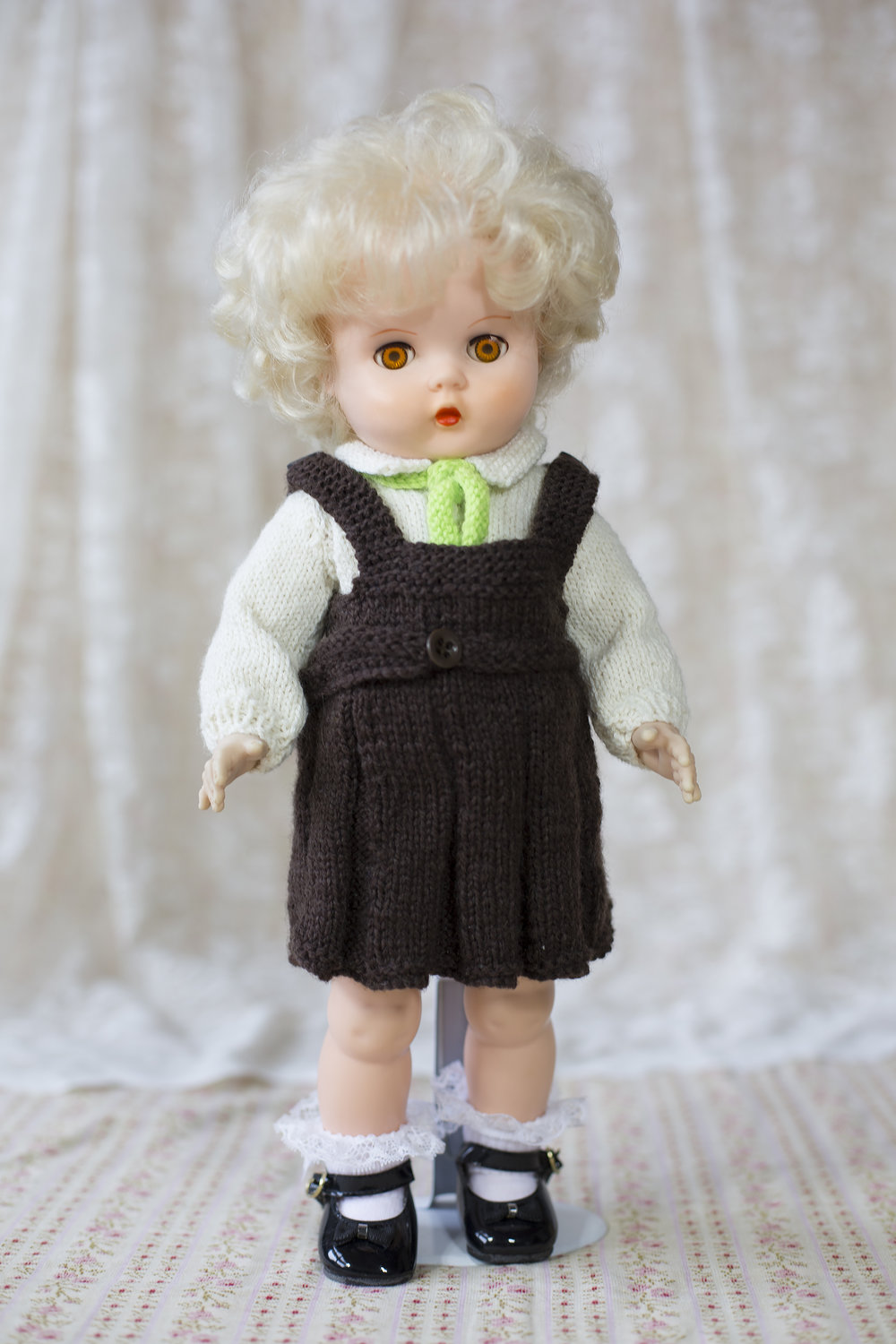 Pedigree doll wearing an Avonside Girls High uniform knitted by Judith in memory of her school days.