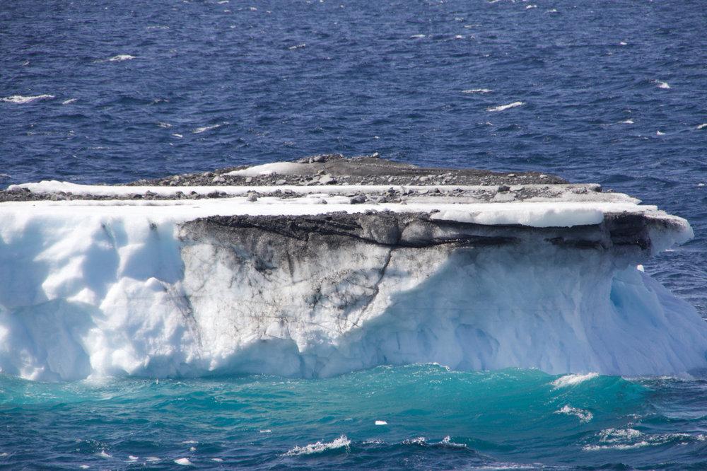 An iceberg transferring debris to the ocean.  Credit: Allison Jacobel