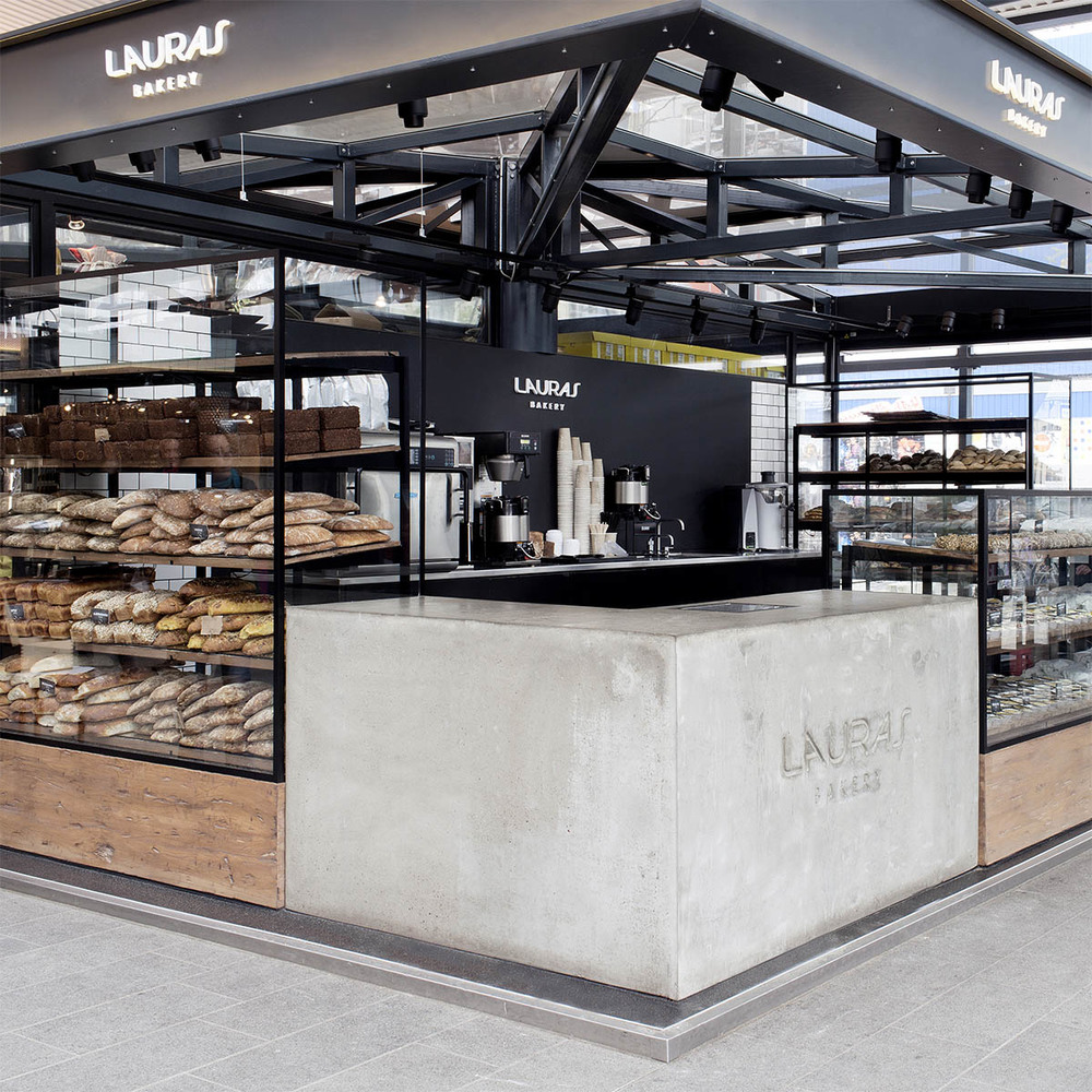 Detail of interior design for Lauras Bakery displaying a concrete corner element decorated with the logo designed by Johannes Torpe Studios