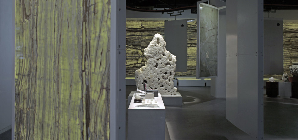 Exhibition panels made of onyx hanged from the ceiling and carried on a conveyor-belt system