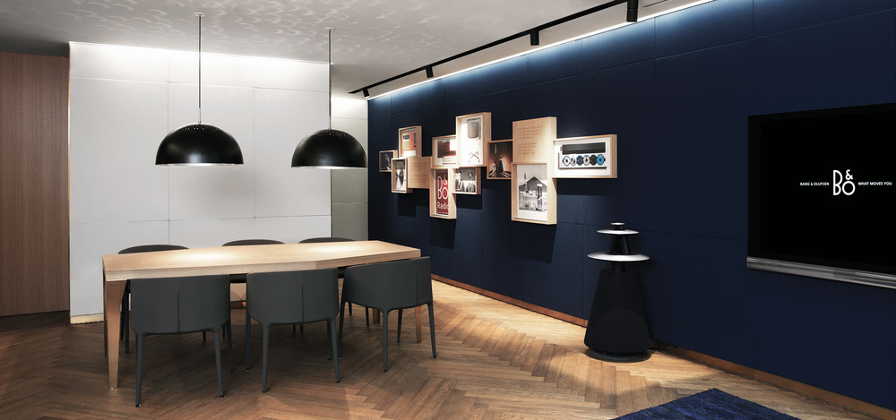 B&O store where TVs and loudspeakers are displayed in a space resembling a welcoming living room with a dining table and lamps