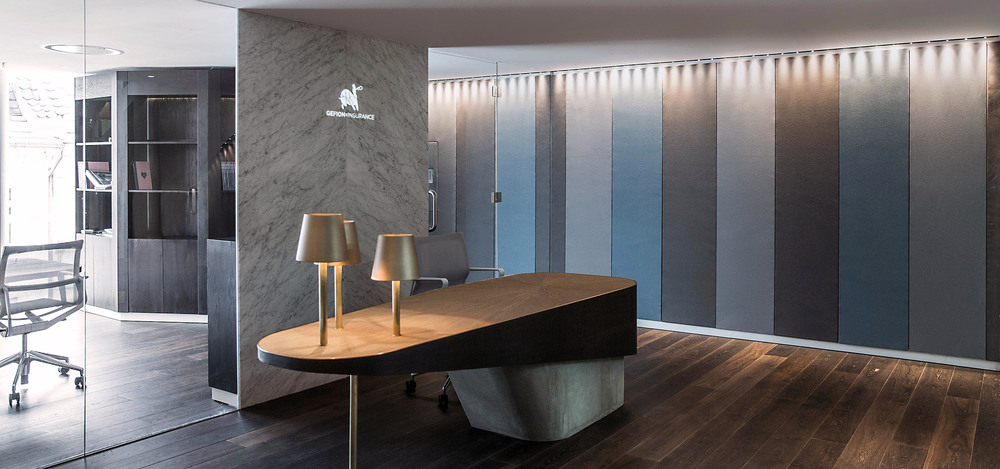 Reception desk with three Tom Dixon lamps at the office of Gefion Insurance in Copenhagen designed by Johannes Torpe