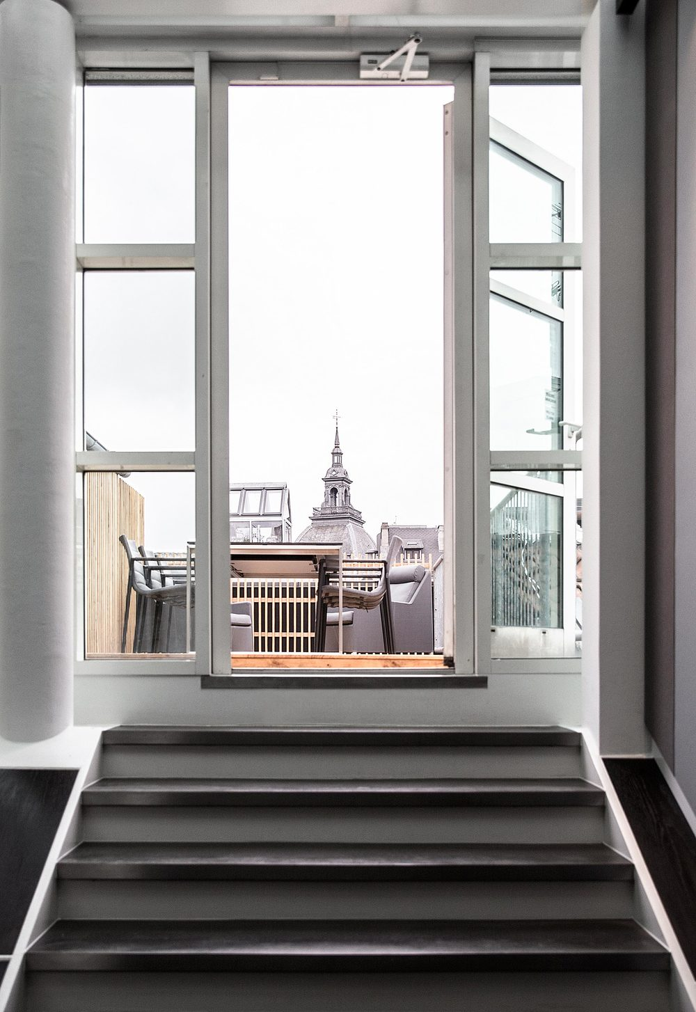 Stairs up to the roof terrace at the Gefion office with a view over the old town of Copenhagen