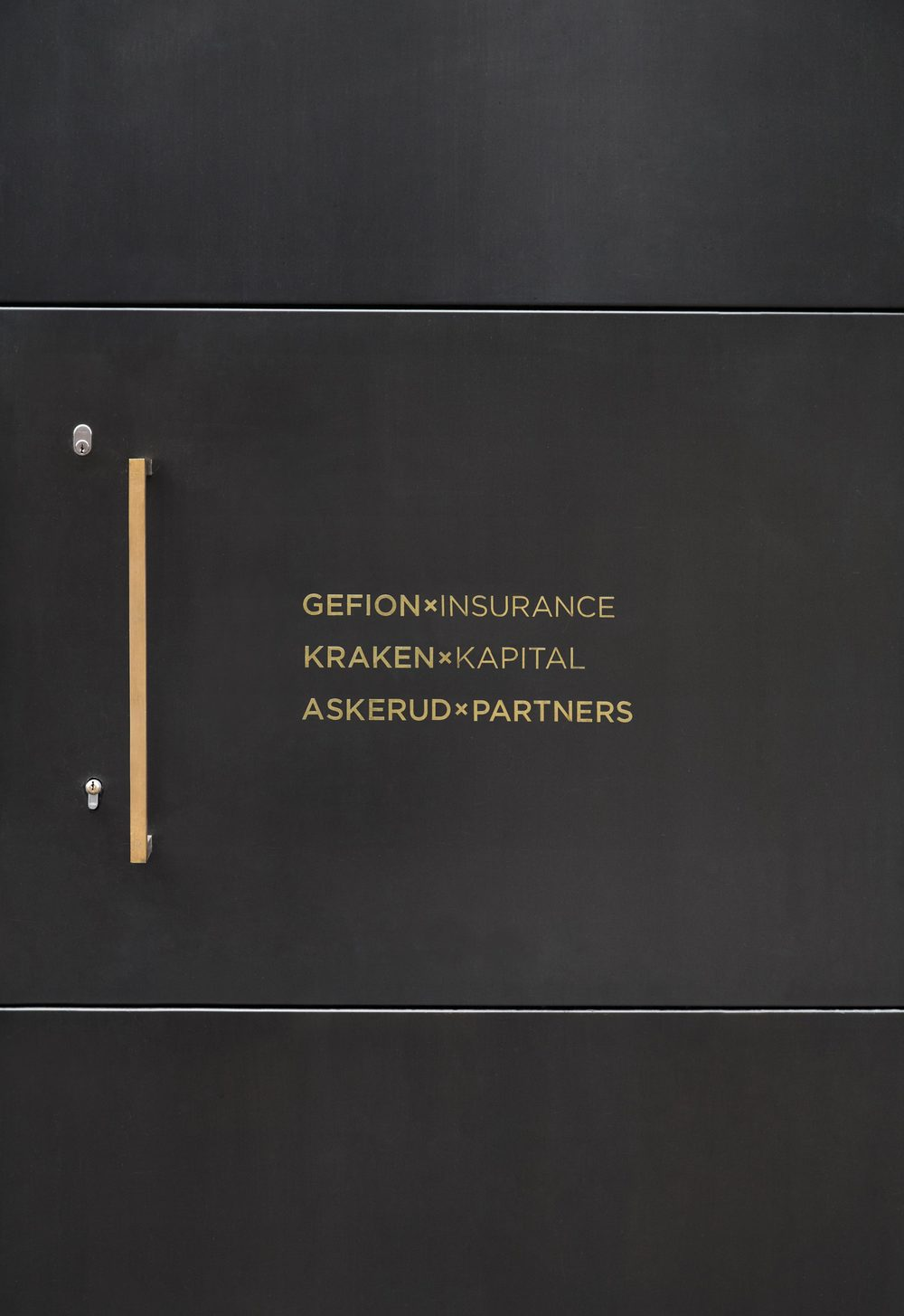 The heavy black front door to Gefion's office carrying company names in brass