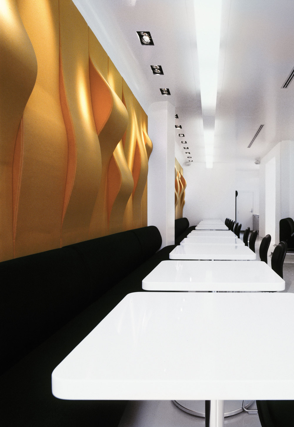 Table row with white tables and black seating next to a wall with wavy orange decoration