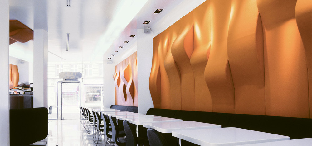 Supergeil restaurant design including a sitting area composed of a long row of black chairs and white tables with wavy orange wall decoration in the back