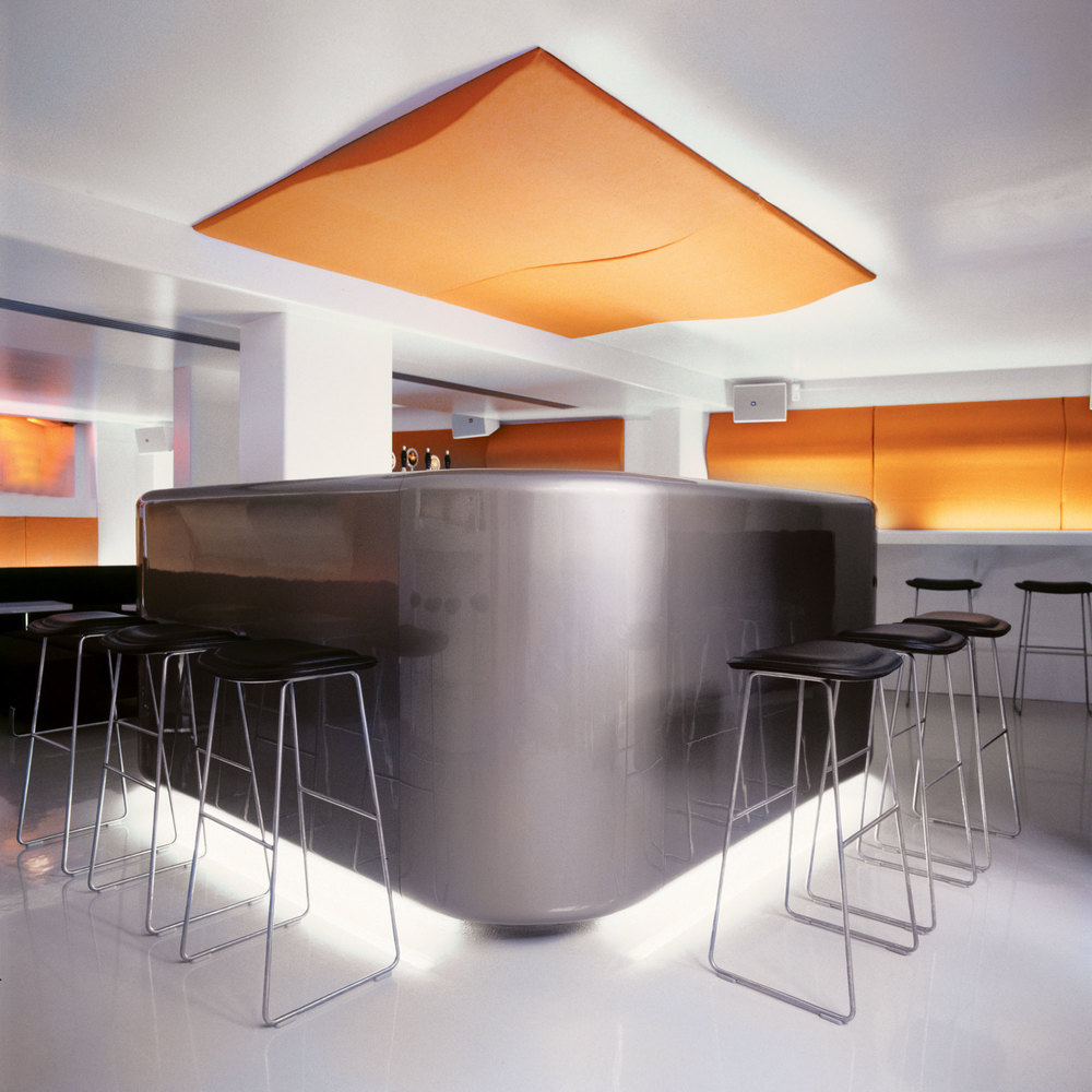 Black barstools standing around a bar which is decorated with an organge fabric panel on the ceiling above