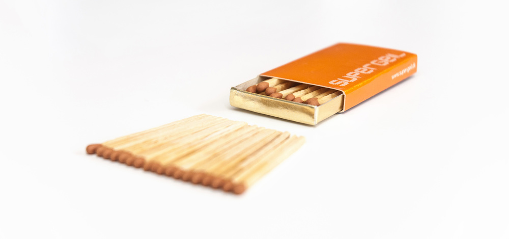 Branded orange Supergeil matchbox with matches matchsticks lying in front of it