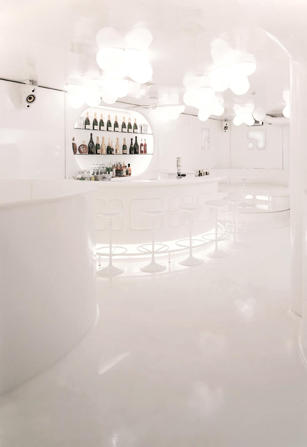 Futuristic white bar stools of NASA Nightclub illuminated by white lights