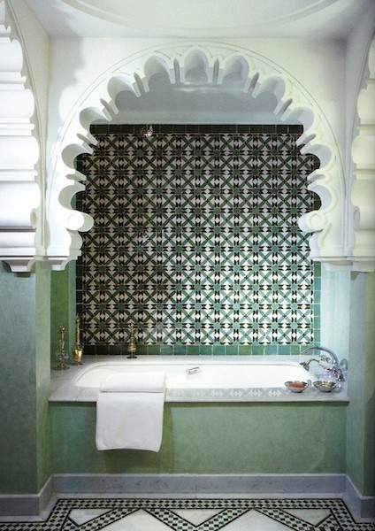 Decorative horseshoearch and classic tilesinseagreen make for beautiful serenity in thisbath alcove.
