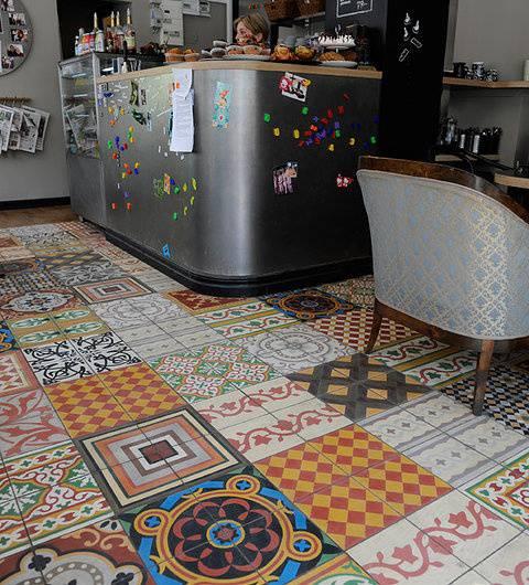 Randomly laid squares of patterned tiles makeup a vibrant patchwork floor.