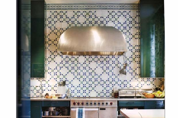 Emerald green cabinets and a wall of tiles -cleverly broken up with blank white tiles to alleviate and refreshthe look of therepetitive pattern.