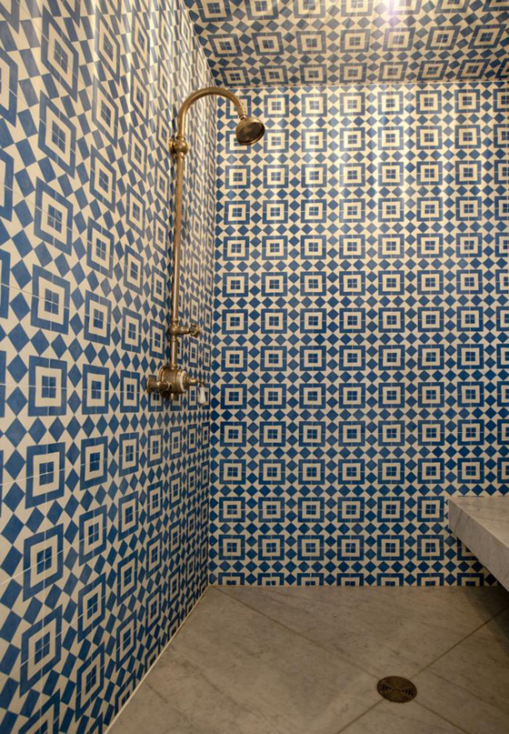 Maximum impact;wall to wall geometrictiles in the walk in shower. Contrasted by plain stone tiles onthe floor and seat.