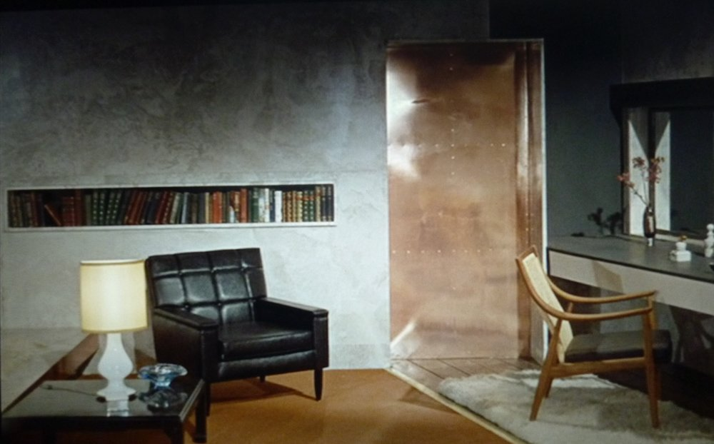 Goldfinger again. We will use the design of the inset shelf; a strong graphic for housing paperback books, (Ike has a huge collection he puts in the rooms). Copper plating like that on the door will be used to clad the shower and freestanding baths.