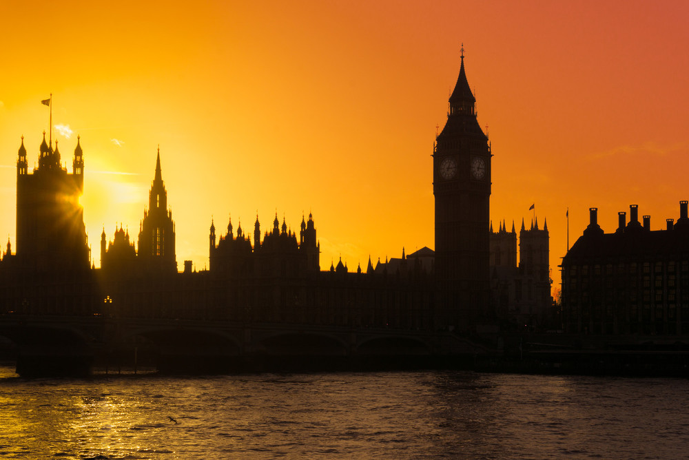 Parliament and Big Ben are show in silhouette with a stunning orange sunset in the background.