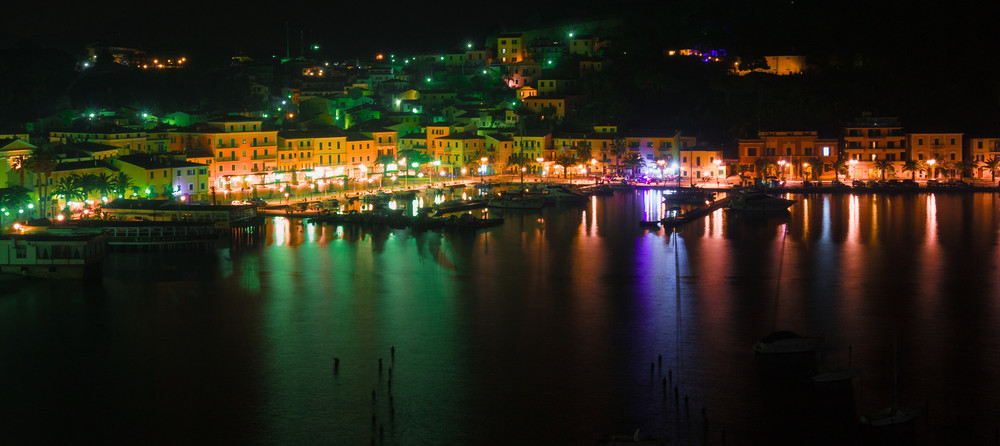 "Elba's ""Blue Port"" becomes a black backdrop for the color harbor lights and traditional Italian sea-side buildings."