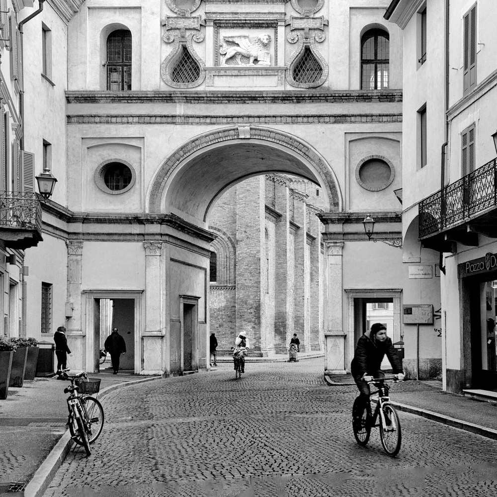 These bikers take advantage of the car-free streets in Crema's limited traffic zone.  The city's cathedral is located behind this classic arch.
