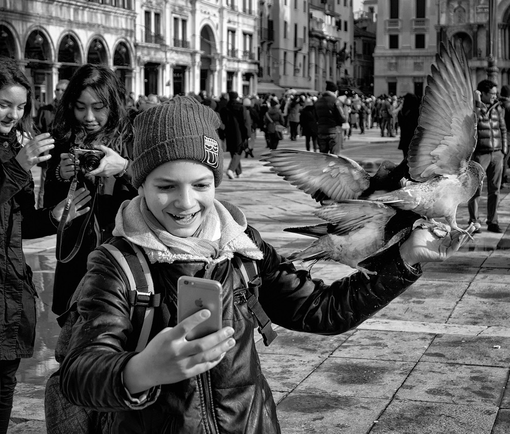 This young man lured pigeons to perch with some small pieces of bread. He had to capture the moment with a selfie.