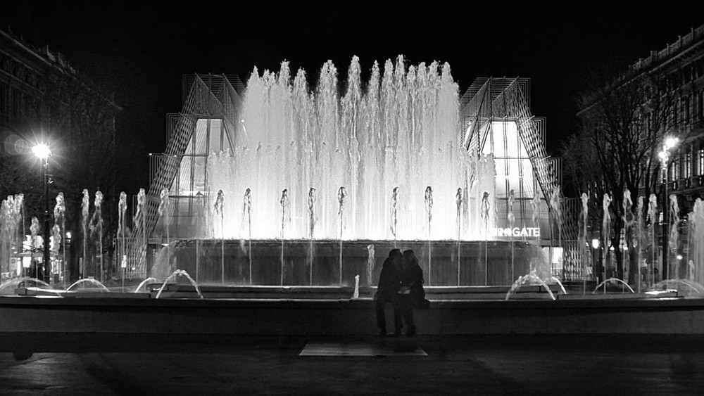 This couple shares a private moment at the fountain outside Castello Sforza in Milan, Italy.  The fountain was recently refurbished ahead of the Expo.