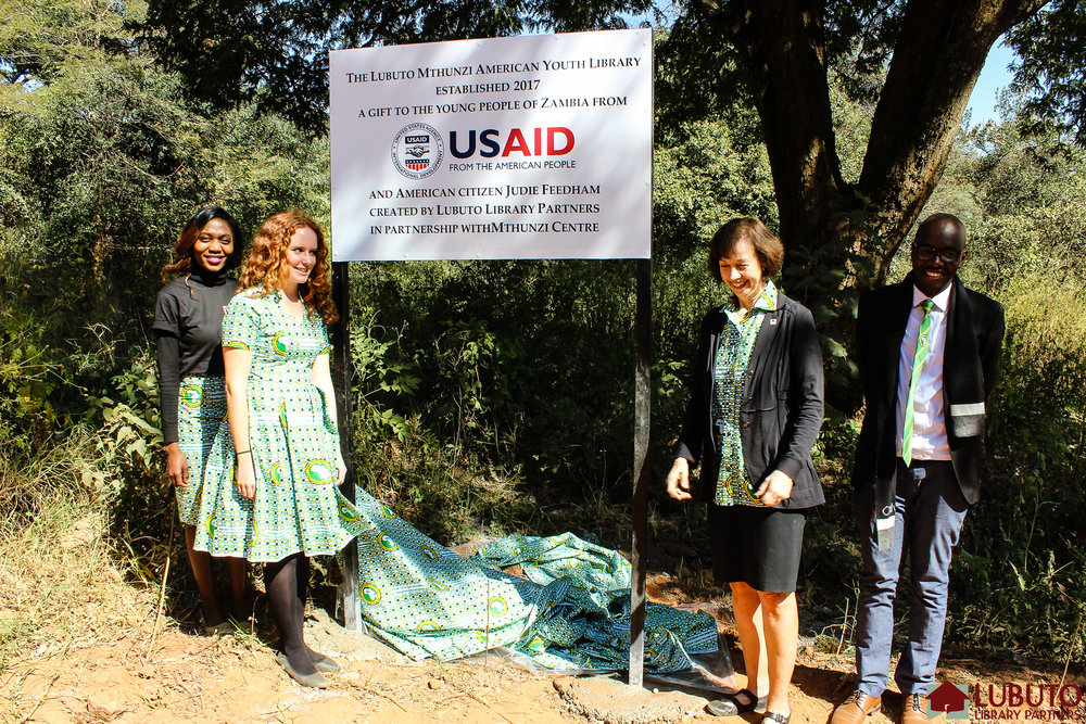 """Lubuto President and Founder Jane Meyers, Country Director Kasonde Mukonde, Director of Library Services Elizabeth Giles and Program Manager Hadassah Kusukumya then—all sporting clothing made with African Library and Information Association and Institution (AfLIA) fabric—raised a AfLIA curtain to reveal the official plaque announcing:     """"The Lubuto Mthunzi American Youth Library established 2017: a gift to the  young people of Zambia from USAID and American citizen Judie Feedham  created by Lubuto Library Partners in partnership with Mthunzi Centre."""""""