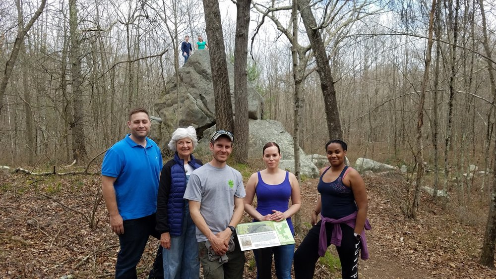 "Massasoit students, professor Susan Martelli, and Wildlands Trust Property Manager Erik Boyer at the 20 ft. boulder, or ""glacial erratic"", at Brockton Audubon Preserve."