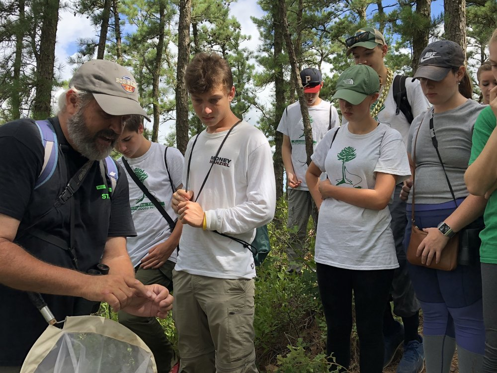 Green Team II crew members observe an insect with Naturalist Jim Sweeney at Great South Pond
