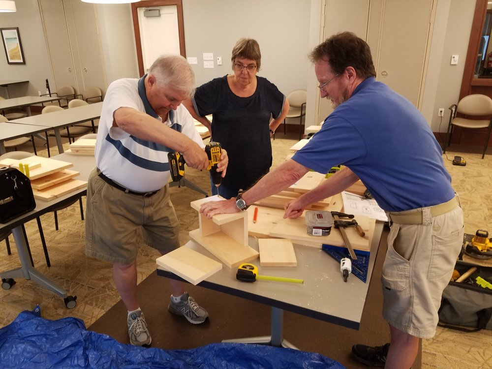 Residents of Fairing Way work together to construct a bluebird box.