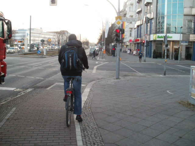 Waiting at a stop light in Berlin.  Notice how the bike lane veers a little right to be back on the sidewalk - completely separated from both motor traffic and foot traffic.  The small triangle just to the left of the bike lane is a left turn holding lane for bikes.