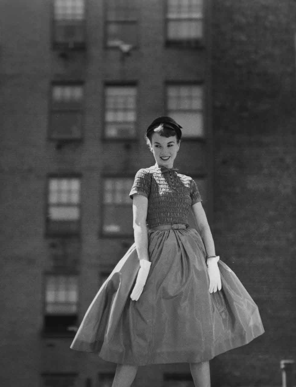 13_55_Model wearing a hat, full dress, and gloves posing on a roof_Dan Wynn Archive 1.jpg