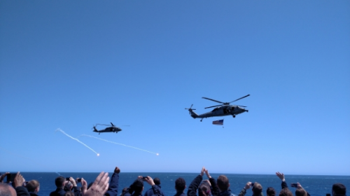 Helicopters flying by carrier