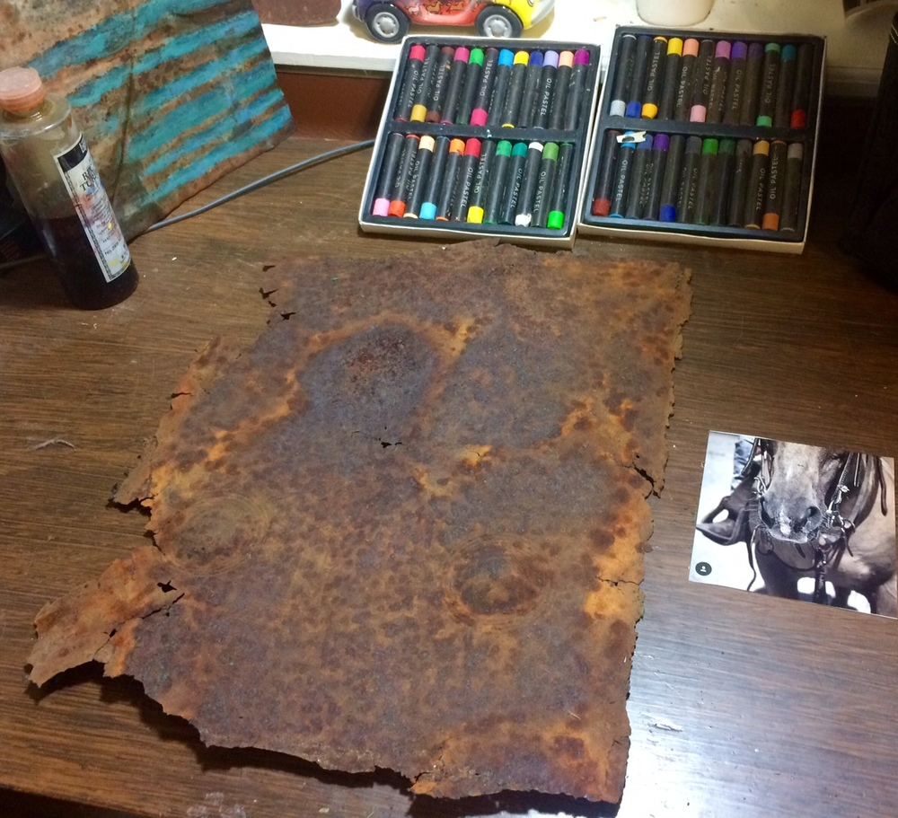 After cleaning and flattening the metal, I set to work with pastels, oils, thinners and scrapers.
