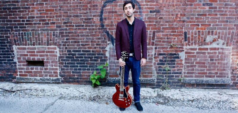 Steve Bilodeau 2015 press photo with guitar. Photo by Elena Snow.