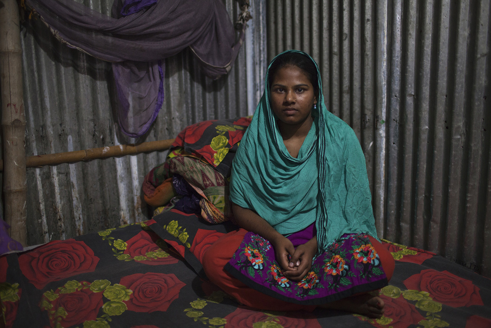Garment worker Semu Begum, 22, who works for Lifestyle Fashions Maker Ltd, sits on the bed inside her rented room in Dhaka, Bangladesh. (Credit: Will Baxter)
