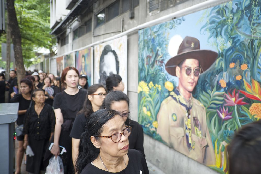 Thais line up around the Royal Palace in Bangkok to pay their final respects to the late Thai King on the one-year anniversary of his death. (Credit: Dene-Hern Chen)