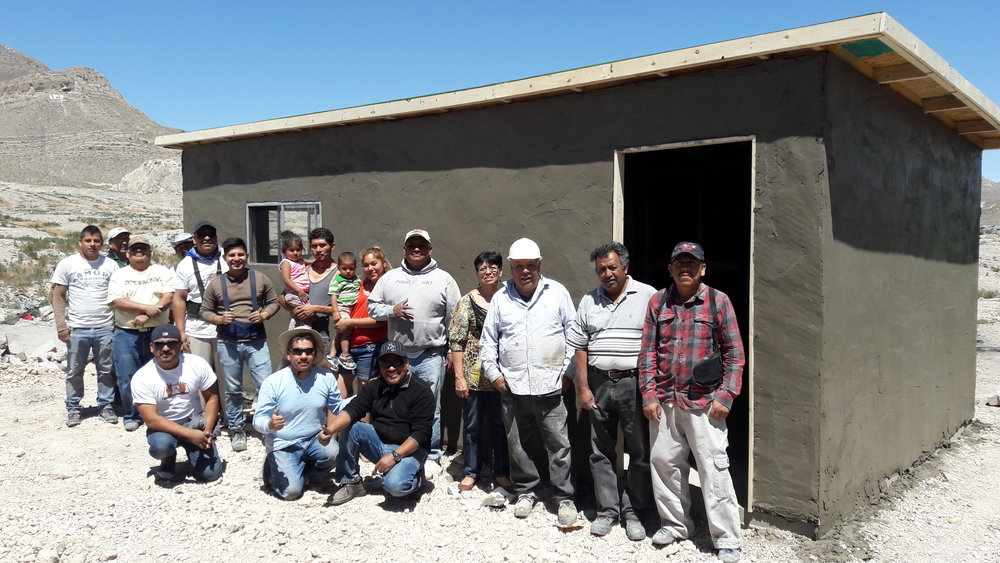 The Aguilera Torche family with the local laborers who built their home.